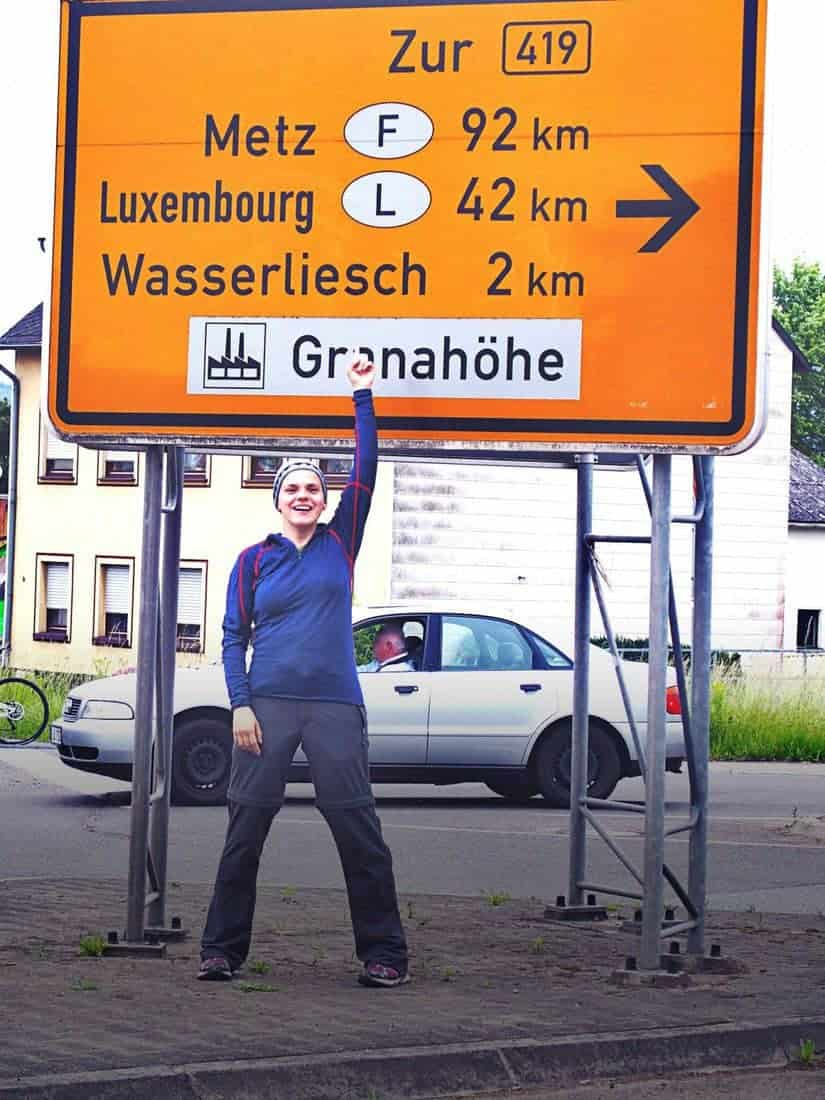 Carola with road sign to Luxembourg and France, Germany (2014-06)