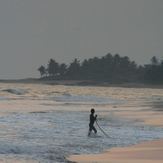 Fisherman in the water at sunset in Brenu Beach, Ghana (2011-12)