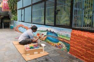 Man painting colorful murals at Cave Villa, Batu Caves, Kuala Lumpur, Malaysia - 20171231-DSC03289