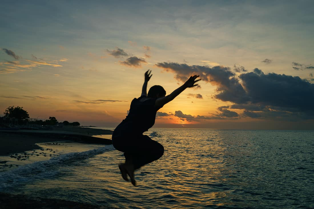 Carola jumping at sunset in Pante Macassar, Oecusse, East Timor